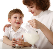 Mother pours milk to son. Mother and child with glass of milk and jug on isolated Stock Image