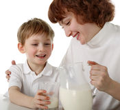 Mother pours milk to son. Mother pours milk to child on isolated Stock Photo
