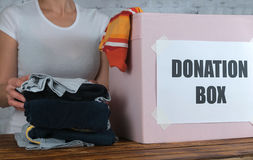 Mother prepare old son`s clothes for donation royalty free stock image
