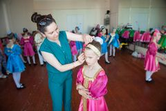 Mother prepares her unhappy daughter for a concert at the dance school. Mother prepares her daughter for a concert at the dance school Stock Photo