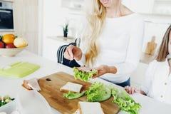 Mother prepares sandwich her daughter home kitchen stock photos