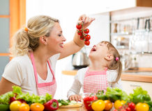 Mother preparing dinner and feeding kid  tomatoes in kitchen Stock Image