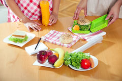 Mother preparing healthy lunch box for child Royalty Free Stock Photos