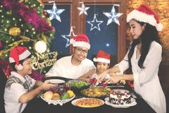Mother preparing meal at Christmas time. Image of young mother preparing meal for her family in dining table while celebrating Christmas at home Stock Photo