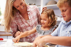 Mother preparing pizza with kids Royalty Free Stock Photography