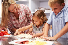 Mother preparing pizza with kids Stock Photos