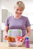 Mother Preparing Unhealthy Lunchbox In Kitchen Royalty Free Stock Image
