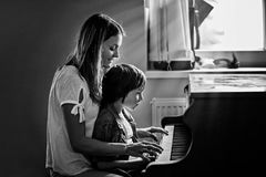 Mother and preschool child, cute boy, playing piano at home Royalty Free Stock Photography