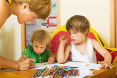 Mother and preschool children playing with pencils Stock Images