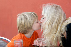 Mother and Preschool Son. Beautiful blond mother kissing her preschool son against orange background Stock Photo