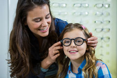 Mother prescribing spectacles to her daughter Royalty Free Stock Image