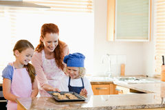 Mother presenting finished cookies to her children Stock Photography