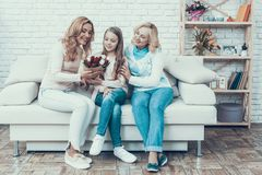 Mother Presents Bouquet of Tulips to Daughter stock images