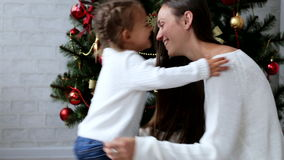 Mother presents a surprise gift box to her daughter at Christmas celebration. Young smiling mother presents a surprise gift box to her cute little daughter and stock video footage