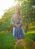 Mother and pretty toddler girl in blossom garden Royalty Free Stock Images