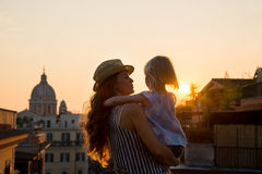 Mother in profile holding daughter in her arms overlooking Rome Stock Images