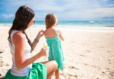 Mother protects her baby from the sun with Stock Images