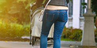 Mother pulling the baby carriage in public street f stock image