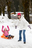 Mother Pulling Daughter On Sledge Royalty Free Stock Photos
