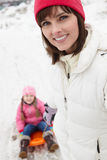 Mother Pulling Daughter On Sledge Stock Photos