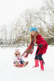 Mother Pulling Daughter On Sledge Through Snow Royalty Free Stock Photo
