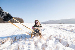 Mother pulling daughter on sledge. Sunny white winter nature. Stock Image