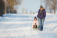 Mother pulling daughter on slegde Stock Photography