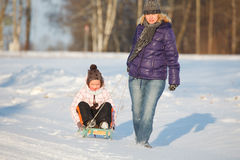 Mother pulling daughter on slegde Royalty Free Stock Photo