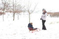 Mother pulling her son on a sled in snow Stock Photo