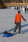 Mother Pulling Son. A young mother pulls her son on a sled while taking a leisurely skate royalty free stock image