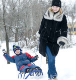 Mother pulling son on sledge Stock Photography