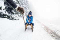 Mother pulling son on sledge. Foggy white winter nature. royalty free stock photos