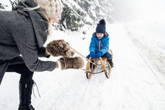 Mother pulling son on sledge. Foggy white winter nature. Royalty Free Stock Image