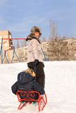 Mother pulling a toboggan with her child in snow Stock Photo