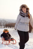 Mother pulling a toboggan with her child in snow Stock Photography
