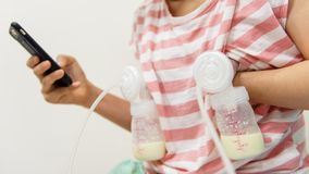 Mom pump breastmilk and play smartphone. Mother pumping milk to bottles by Automatic breast pump machine while play social media, chat, and shopping online from stock image