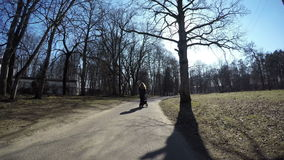 Mother push blue baby carriage in spring park. 4K stock video footage