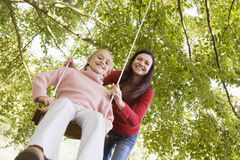 Mother pushing daughter on swing Stock Photography
