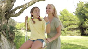 Mother pushing daughter on the swing Royalty Free Stock Photos