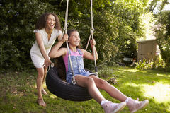 Mother Pushing Daughter On Tire Swing In Garden Royalty Free Stock Photography