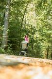 Mother pushing her baby in a pram or stroller Stock Image