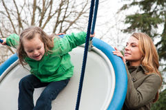 Mother pushing her daughter on a swing Stock Photo