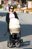 Mother pushing pram. Young mother with sunglasses pushing pram on pavement or sidewalk Royalty Free Stock Image