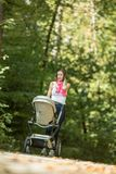 Mother pushing a pram or baby carriage along a rural road throug. H forest in autumn in a low angle view Royalty Free Stock Photography