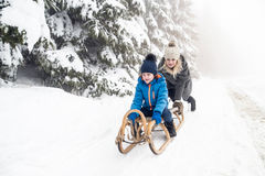 Mother pushing son on sledge. Foggy white winter nature. Royalty Free Stock Image