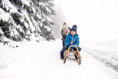 Mother pushing son on sledge. Foggy white winter nature. stock photo