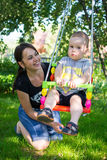 Mother pushing son on swing Stock Image