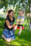 Mother pushing son on swing Stock Photos