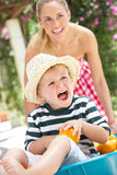 Mother Pushing Son In Wheelbarrow Stock Image
