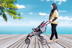 Mother pushing stroller at beach Royalty Free Stock Photography